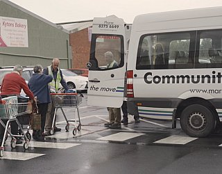 Community Bus At Shopping Centre With Residents